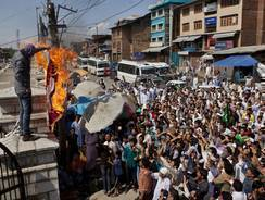 A Kashmiri Muslim with his face covered burns a mock American flag as others shout slogans during a protest Friday in Srinagar, India.