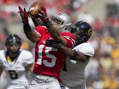 Ohio State wide receiver Devin Smith pulls in a long pass under pressure from California defensive back Steve Williams.