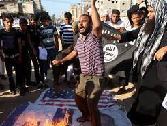 Palestinian protesters burn a picture of President Obama along with U.S. and Israeli flags during a demonstration on Friday in Rafah in the southern Gaza Strip.