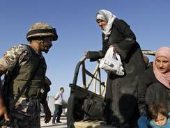 A Jordanian soldier helps Syrian refugees who have fled violence in their country after having crossed the border into Jordanian territory with their families near the town of Ramtha.