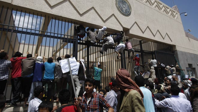 Yemeni protestors climb the gate of the U.S. Embassy during a protest Sept. 13.