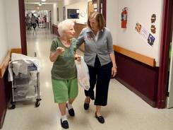 Resident Irene DuRell walks the hallways with administrator Jill Herron at Welcome Nursing Home in Oberlin, Ohio.