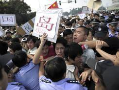 Chinese workers attempt to break through a police line in central China's Hubei province. The 81st anniversary of a Japanese invasion brought a fresh wave of anti-Japan demonstrations in China on Tuesday.