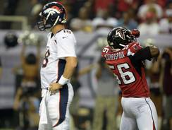 Broncos quarterback Peyton Manning (18) and Falcons linebacker Sean Washington (56) react during Monday night's game.