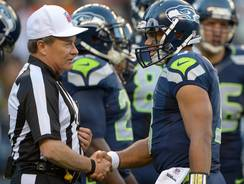 Seattle Seahawks quarterback Russell Wilson shakes hands with replacement referee Jerry Frump during a game against the Oakland Raiders.