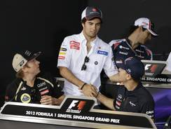 F1 driver Sergio Perez, center, shakes the hand of Red Bull driver Sebastian Vettel of Germany as Kimi Raikkonen of Finland looks on Thursday in Singapore.