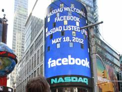 Tourists view Nasdaq's giant monitor in New York's TImes Square  as it shows a welcome message for Facebook before the company began trading on the Nasdaq stock market on May 18, 2012.