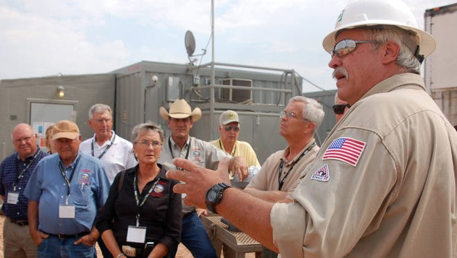 Hess drilling supervisor Mike Durkin explains the oil-drilling process to lawmakers from North and South Dakota Aug. 30, 2012, near Tioga, N.D. The oil boom has helped employment in both states.