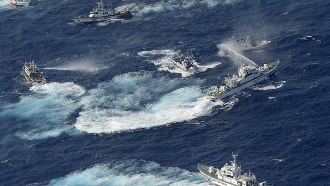 A Japanese coast guard vessel, right, sprays water against Taiwanese fishing boats while a Taiwanese coast guard ship, left, also sprays water in the East China Sea in Sept.