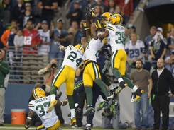 Seahawks receiver Golden Tate (81) catches a controversial 24-yard touchdown pass as Packers players try to intercept it.