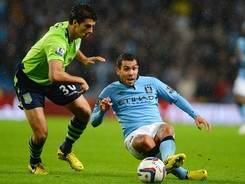 Manchester City's Carlos Tevez slips as he's defended by Aston Villa's American defender Eric Lichaj during City's 4-2 League Cup loss.