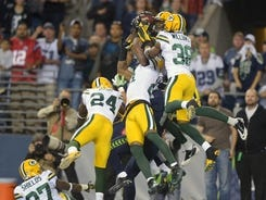 Packers and Seahawks players fight for control of the controversial final pass of Monday night's game.