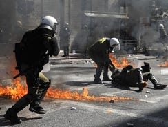 Riot police react amid firebombs thrown during clashes in Athens on Wednesday.
