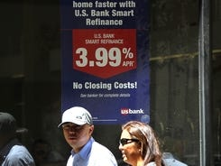 Pedestrians pass by a sign advertising low refinance rates at a US Bank office on June 7, 2012, in San Francisco.