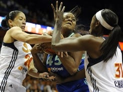 The Sun's Kara Lawson, left, and Tina Charles, right, pressure the Liberty's Kara Braxton during Game 1 of their first-round playoff series in Uncasville, Conn.