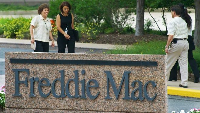 People walk by a sign for Freddie Mac headquarters in McLean, Va.