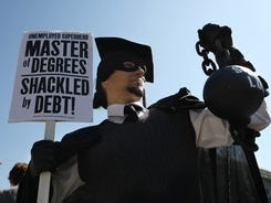 "Gan Golan, of Los Angeles, dressed as the ""Master of Degrees,"" holds a ball and chain representing his college loan debt, during Occupy DC activities in Washington, Oct. 6, 2011."
