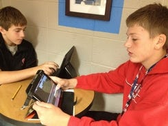Michael Lang, left, and Bryce Seubert, students at Marathon (Wis.) Venture Academy, work on video projects using their iPads during a study period on Sept. 26, 2012. The academy loaned 135 iPads to students last year. Of those, 25 needed repairs.