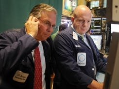 Michael O'Connor, right, of Getco Securities and a fellow trader work on the floor of the New York Stock Exchange in September 2012.