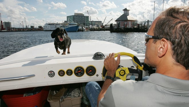 Fane Lozman and pet dog Lady in his speed boat near the Marina in Riviera Beach, Fla.