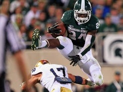 Spartans running back Le'Veon Bell leaps over Notre Dame safety Zeke Motta two weeks ago.