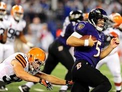 Ravens quarterback Joe Flacco (5) runs away from Browns linebacker Scott Fujita (99) at M&T Bank Stadium.