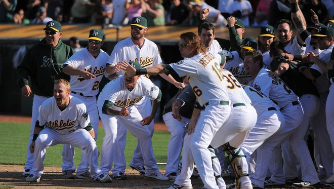 Athletics players gather at home plate to congratulate teammate Brandon Moss (not pictured), who hit a game-winning three-run homer in the 10th inning to beat the Mariners.