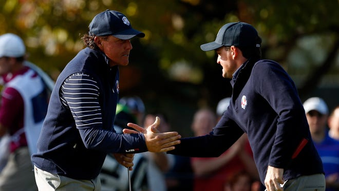 Phil Mickelson, left, and Keegan Bradley celebrate a birdie putt on the ninth hole during the morning foursome matches on Day 2 of the Ryder Cup.