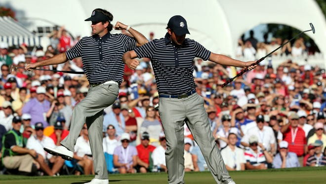 Bubba Watson, left, and Webb Simpson celebrate a Simpson birdie on 13 on their way to a fourball victory Saturday at the Ryder Cup.