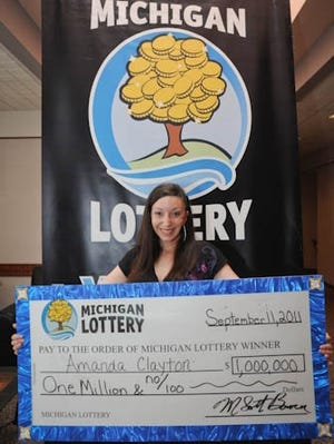 Amanda Clayton holds her ceremonial $1 million lottery check. She collected welfare despite winning the prize and later was sentenced to probation.