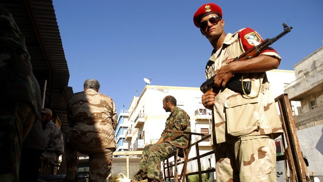 Libyan security forces stand guard as people turn in weapons in Benghazi, Libya, on Sept. 29.