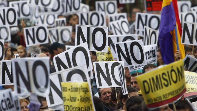 "Protestors hold banners including ones reading ""NO"" and ""Resign!""  during the demonstration against austerity measures announced by the Spanish government, in Madrid, Spain, Sept. 29."