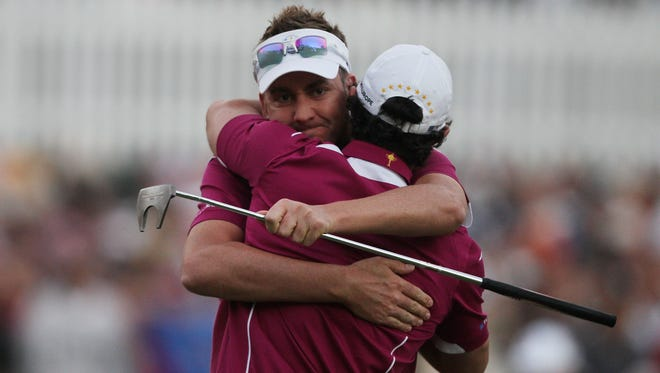 Ian Poulter embraces playing partner Rory McIlroy after the duo rallied to defeat Jason Dufner and Zach Johnson on Saturday.