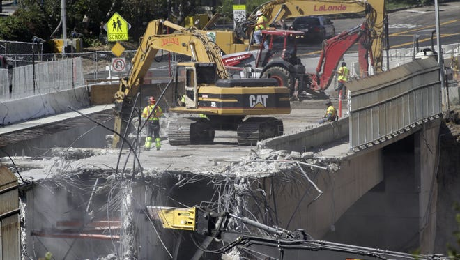 Crews work Saturday to demolish a portion of the Mulholland Drive bridge that spans I-405 in Los Angeles.