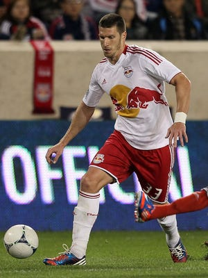 Kenny Cooper (33) of the New York Red Bulls brings the ball up the field against Ashtone Morgan (5) of Toronto FC at Red Bull Arena.