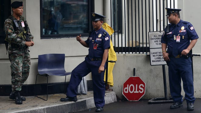 Armed policemen secure the entrance to the U.S. embassy compound known as 'Seafront' in Pasay, a major district in the capital Saturday.