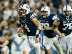 BYU quarterback Taysom Hill scrambles for a touchdown in the first half.