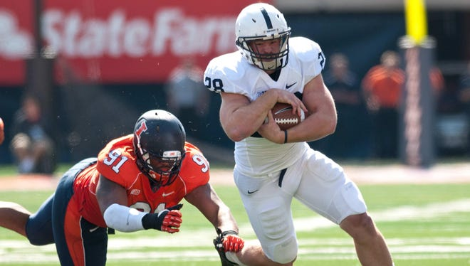 Penn State running back Zach Zwinak (28) tries to avoid a tackle by Illinois defensive lineman Glenn Foster (91) during the second quarter at Memorial Stadium.
