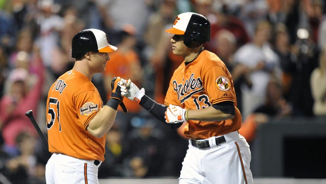 The Orioles' Manny Machado, right, gets a fist bump from teammate Lew Ford after hitting a go-ahead solo home run in the seventh inning.