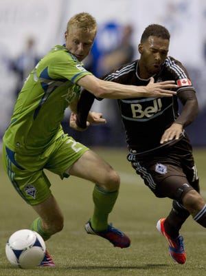 Vancouver Whitecaps FC Matt Watson, right, fights for control of the ball with Seattle Sounders FC Andy Rose during second half of MLS soccer action.
