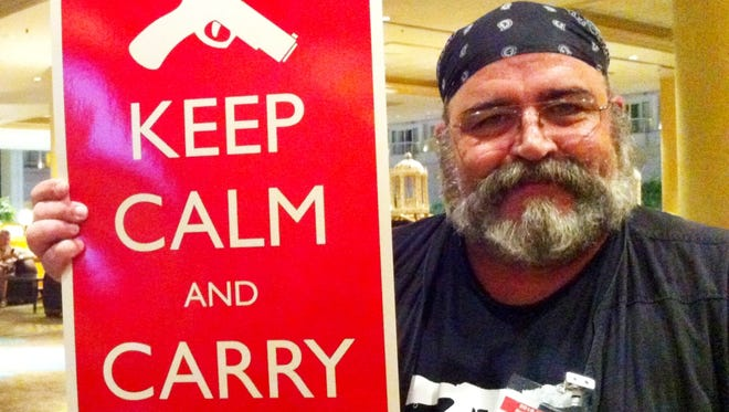 Miguel Gonzalez, 52, of Miami displays a sign that was sold at the 27th annual Gun Rights Policy Conference in Orlando.