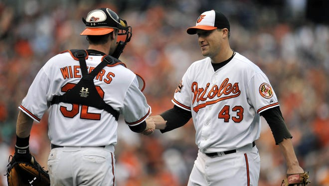 Orioles pitcher Jim Johnson, left, and catcher Matt Wieters shake hands their win over the Red Sox.