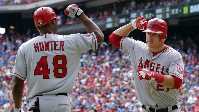 Mike Trout, right, celebrates his solo home run with Torii Hunter.