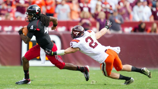 Bearcats quarterback Munchie Legaux evades a sack from Virginia Tech linebacker Michael Cole during Saturday's game. Cincinnati enters the poll this week at No. 23.