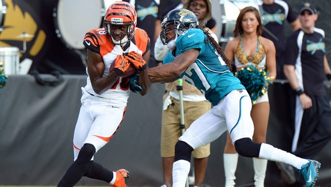 Bengals wide receiver A.J. Green (18) hauls in a 42-yard pass to the 1-yard line while defended by Jaguars cornerback Rashean Mathis on Sunday.