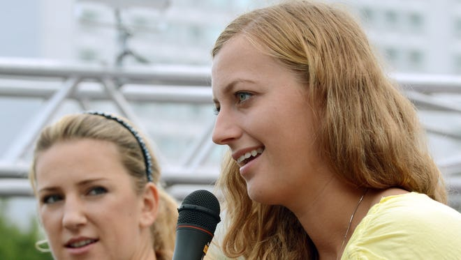 Petra Kvitova of Czech Republic at the microphone, where she is becoming increasingly comfortable, with Victoria Azarenka looking on.