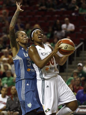 Storm guard Tanisha Wright, right, driving to the basket against Lynx guard Seimone Augustus, tallied 18 points and seven assists to lead Seattle to an 86-79 double-overtime win.