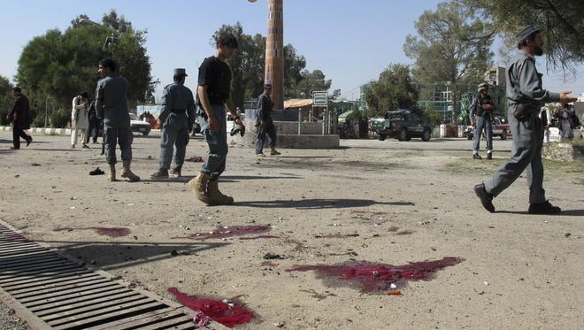 Afghan police secure the site of a deadly suicide bombing in Khost, Afghanistan, Oct. 1, 2012.