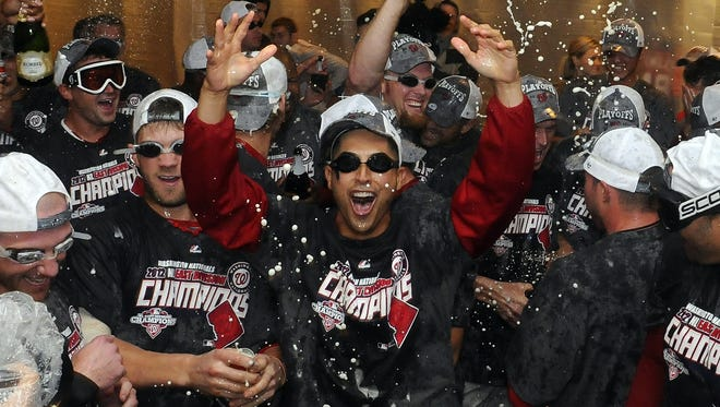 Gio Gonzalez, center, and Bryce Harper, left celebrate in the Nationals clubhouse.