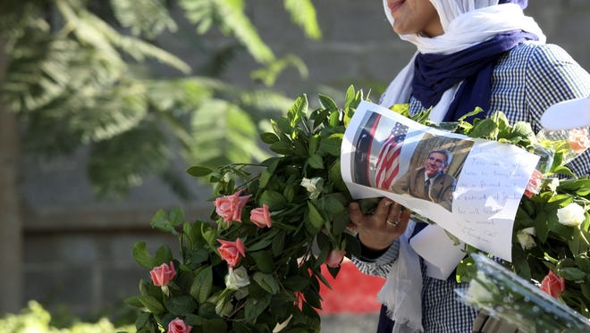 Salwa Bugaighis carries a wreath with a photo of U.S. Ambassador Chris Stevens as she and others gather to pay their respect to the victims of the attack at the U.S. Consulate in Benghazi.